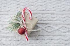 Il regalo di Natale con il bastoncino di zucchero su bianco ha tricottato il fondo Fotografie Stock