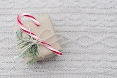 Il regalo di Natale con il bastoncino di zucchero su bianco ha tricottato il fondo Immagini Stock Libere da Diritti
