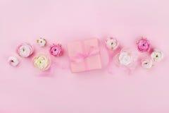 Il regalo o la scatola e la molla attuali fioriscono sullo scrittorio rosa da sopra per il modello di nozze o la cartolina d'augu immagini stock