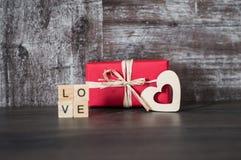 Il regalo in scatola rossa, il cuore di legno e la parola amano, allineato con Immagine Stock