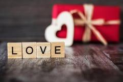 Il regalo in scatola rossa, il cuore di legno e la parola amano, allineato con Immagini Stock