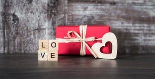 Il regalo in scatola rossa, il cuore di legno e la parola amano, allineato con Immagine Stock Libera da Diritti