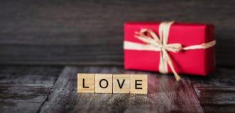 Il regalo in scatola rossa e la parola amano, allineato con i blocchi di legno, sul da Fotografia Stock Libera da Diritti
