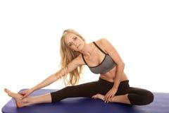 Il reggiseno di sport di gray della donna si siede lo sguardo della gamba di allungamento Fotografia Stock Libera da Diritti