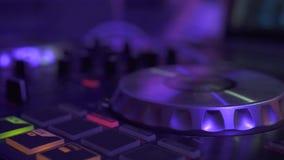 Il regolatore del DJ per musica mescolantesi sul partito di notte e la luce variopinta in discoteca bastonano Chiuda sul giocator stock footage