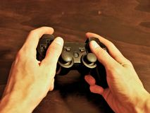 Il regolatore di console del video gioco per gioco ha tenuto in mani dei gamers immagini stock