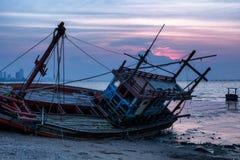 Il relitto è stato lasciato sulla spiaggia con il bello cielo crepuscolare Immagine Stock