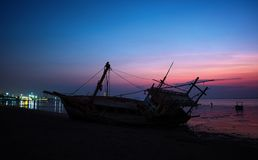 Il relitto è stato lasciato sulla spiaggia con il bello cielo crepuscolare Fotografia Stock Libera da Diritti