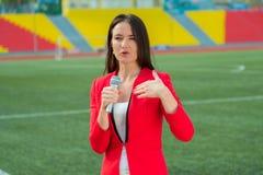 Il reporter della ragazza TV sta trasmettendo per radio fotografia stock