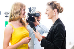 Il reporter ed il cineoperatore sparano un'intervista Immagini Stock