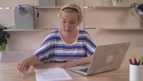 Il responsabile adulto lavora nella seduta scocciata il cattivo umore nel luogo di lavoro con il computer portatile stock footage