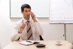 Il responsabile comunica dal telefono Fotografie Stock Libere da Diritti