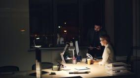 Il responsabile di società sta parlando con il suo impiegato che lavora tardi con il computer alla notte che dà gli ordini e che  archivi video