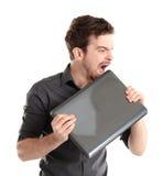 Il responsabile di ufficio irritato morde il computer portatile Fotografia Stock
