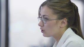 Il responsabile femminile attraente che parla con il cliente in ufficio, spiegante condiziona stock footage
