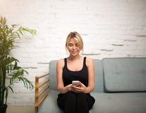 Il responsabile femminile sorridente che chiacchiera sul cellulare durante il lavoro irrompe la società Fotografie Stock Libere da Diritti