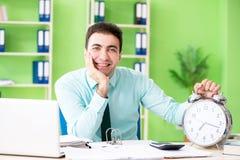 Il responsabile finanziario maschio che lavora nell'ufficio nel concetto della gestione di tempo Fotografia Stock