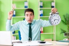 Il responsabile finanziario maschio che lavora nell'ufficio nel concetto della gestione di tempo Fotografie Stock