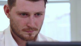 Il responsabile maschio esamina lo schermo del computer portatile archivi video