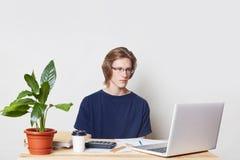 Il responsabile maschio serio dirige le finanze a casa, utilizza il computer portatile ed il calcolatore, esamina i grafici con l immagini stock libere da diritti
