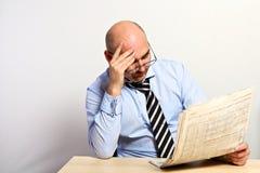 Il responsabile studia la parte finanziaria di un giornale Immagini Stock