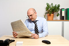 Il responsabile studia la parte finanziaria di un giornale Immagini Stock Libere da Diritti