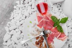 Il resti di alimento costoso su un piatto ceramico con un coltello e sulla forcella su un bianco lapida il fondo Un vetro di ross Fotografia Stock