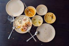 Il resti di alimento in piatti, in briciole sulla tavola dopo pranzo o in cena immagini stock