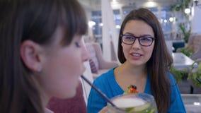 Il resto in caffè, ragazze allegre dagli occhiali comunica durante il brunch in ristorante archivi video