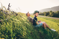 Il resto del figlio e del padre in alta erba verde dopo la bicicletta cammina Fotografia Stock Libera da Diritti