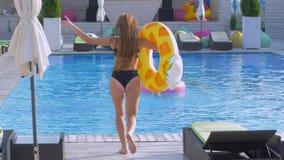 Il resto dell'estate, ragazza felice si rilassa in anelli gonfiabili in poolside e l'amica salta accanto per innaffiare con spruz video d archivio