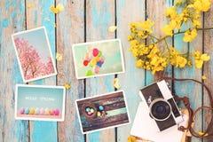 Il retro album di foto della carta e della macchina fotografica sulla tavola di legno con il confine dei fiori progetta Fotografie Stock