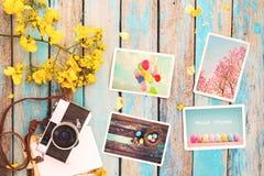 Il retro album di foto della carta e della macchina fotografica sulla tavola di legno con il confine dei fiori progetta Immagini Stock