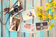Il retro album di foto della carta e della macchina fotografica sulla tavola di legno con il confine dei fiori progetta fotografia stock