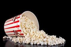 Il retro contenitore rosso e bianco di popcorn si è rovesciato sul nero fotografia stock
