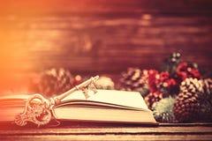 Il retro libro ed il pino vicino chiave si ramifica su una tavola Fotografia Stock Libera da Diritti