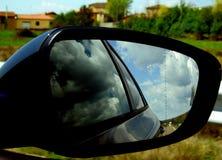 Il retrovisore di un'automobile con le riflessioni delle nuvole fotografia stock libera da diritti