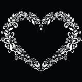 Il ricamo ha ispirato la forma del cuore nel bianco con gli elementi floreali su fondo nero Fotografia Stock Libera da Diritti