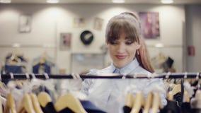 Il ricerca allegro della giovane donna vestiti nuovi su uno scaffale in un negozio di vestiti ma si allontana archivi video