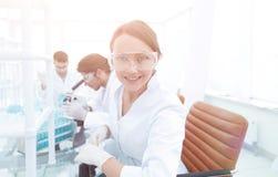 Il ricercatore che controlla le provette, donna indossa gli occhiali di protezione Fotografia Stock