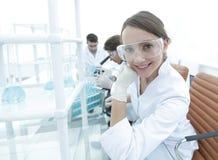 Il ricercatore che controlla le provette, donna indossa gli occhiali di protezione Fotografia Stock Libera da Diritti