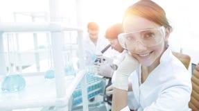 Il ricercatore che controlla le provette, donna indossa gli occhiali di protezione Immagini Stock Libere da Diritti