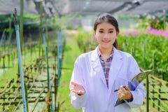 Il ricercatore della giovane donna in un vestito bianco, sfoglia su ed esplora il giardino prima della piantatura dell'orchidea n immagine stock