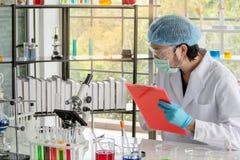 Il ricercatore dello scienziato degli uomini sta riunendo i dati in laboratorio immagine stock