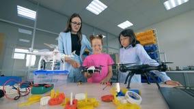 Il ricercatore femminile e due scolari stanno esplorando i fuchi Innovazione nel concetto di istruzione stock footage