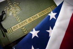 Il ricordo del veterano di Giorno dei Caduti con l'album e la bandiera di servizio militare. Fotografie Stock Libere da Diritti