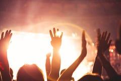 Il riflettore luminoso splende sulla gente ballante Il pubblico applaude i musicisti Siluetta di una folla di concerto immagine stock libera da diritti