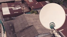 Il riflettore parabolico ha installato sulla cima di costruzione fra i bassifondi arrugginiti dei vecchi tetti matal dello zinco fotografia stock libera da diritti