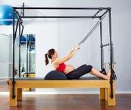 Il riformatore dei pilates della donna incinta rotola sull'esercizio Immagini Stock Libere da Diritti