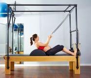 Il riformatore dei pilates della donna incinta rotola sull'esercizio Fotografie Stock Libere da Diritti
